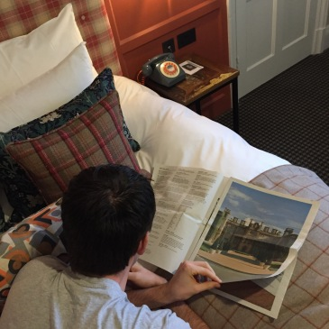 On the bed reading the Eynsham Hall Hotel newspaper